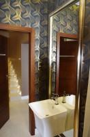 Toaleta dopasowana kolorystycznie oraz stylem do całego parteru domu, wykonana w ciekawej, złoto-czarnej tapecie.