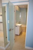 Łazienka w kawalerce w kolorystyce zimnego błękitu, przełamana kolorem drewna. Styl nowoczesny.