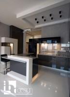 Nowoczesne, biało-czarne wnętrze w prostych formach przenikających się brył, meble w połysku z półwyspem lewitującym nad podświetlaną białą podłogą, ściany w wykończeniu betonowym i pomalowane białą farbą. Kuchnia połączona z meblami pokojowymi, w części salonowej sufit napinany z podświetleniem rgb.