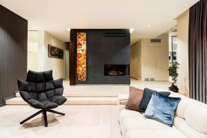 Salon usytuowany w otwartej przestrzeni z jadalnią i holem, wydzielony indywidualnie zaprojektowanym kominkiem.