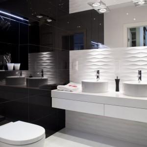 Większa łazienka przeznaczona jest zarówno dla domowników, jak i gości. Połysk i przestrzenna faktura płytek ceramicznych zapewniają ciekawą grę świateł. Płytki Colour White&Black, Tubądzin, miska wc Meridian-N, Roca. Fot. Aleksander Rutkowski.