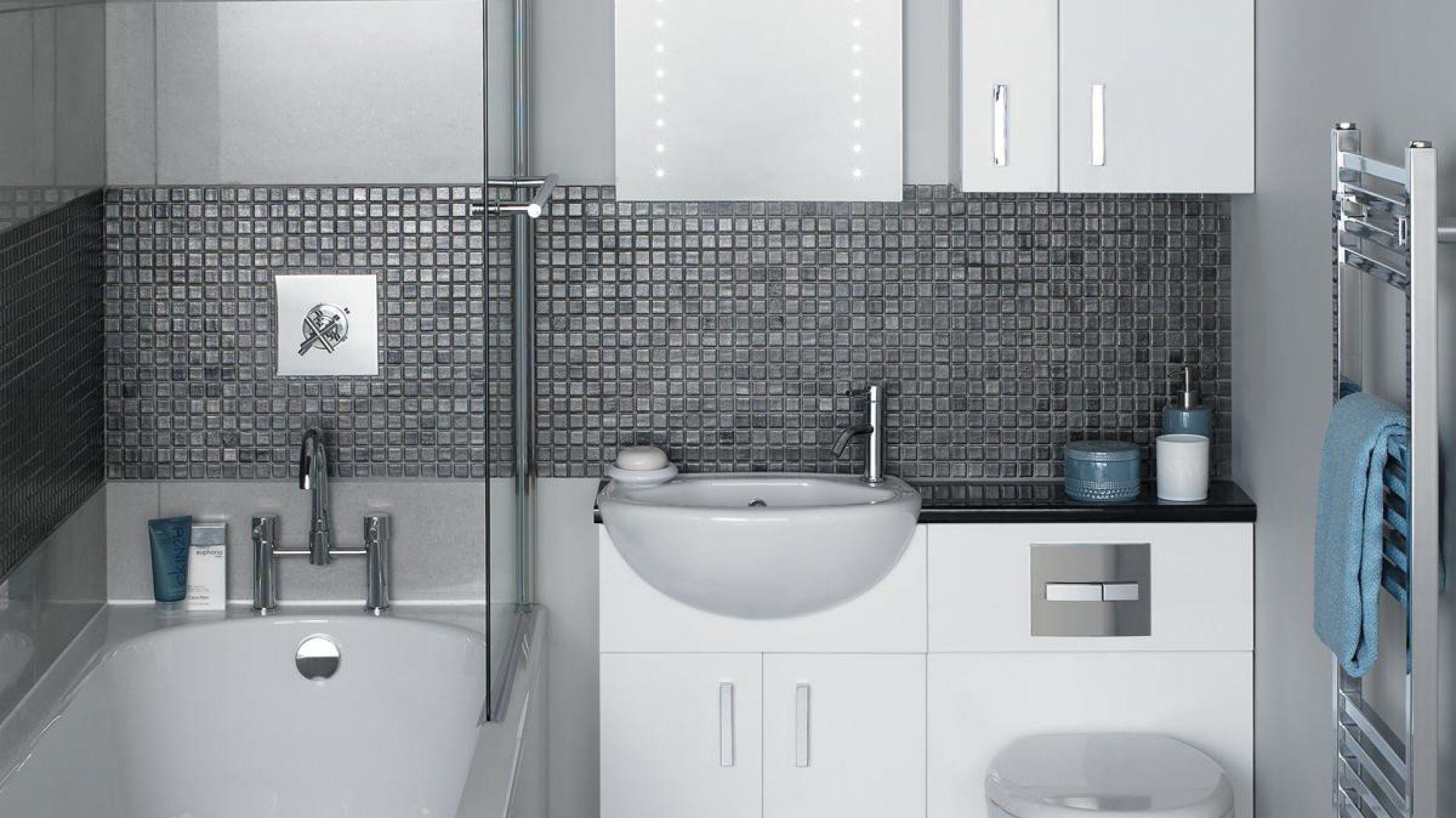Wanna ze szklanym parawanem. Umywalkę i miskę ustępową zamontowano na stelażach tworząc jedną linię zabudowy z szafką podumywalkową. Fot. About Interior Design.