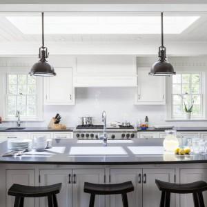 Uwagę zwraca oświetlenie wyspy lampami przemysłowymi, przełamującymi stylistykę retro. Fot. Patrick Ahearn Architects.