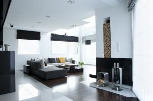 Wnętrze nowoczesne i minimalistyczne. Dzięki temu, że pomieszczenia są wysokie, a szerokie okna wpuszczają duża ilość światła, możliwe było zastosowanie ciemnych barw i ciężkich materiałów.Szklana klatka schodowa dodaje lekkości i sprawia, że pomieszczenie jest jeszcze bardziej przestronne i ciekawe.