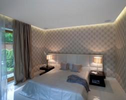 W sypialni znajdziemy klasyczne tapety, delikatne tkaniny i ciepłe kolory, które sprawiają, że sen jest jeszcze przyjemniejszy. Delikatne oświetlenie dodaje klimatycznego nastroju, a panoramiczne okno wita widokiem przydomowego ogrodu