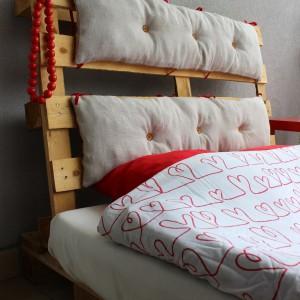 """Łóżko """"Pikuś"""" wykonane z palet. Wykończone dwoma pikowanymi poduszkami, które wykonano z lnianych, nieużywanych worków wojskowych z lat 60tych. Poduszki przymocowane są do palet czerwonymi wstążkami i pikowane drewnianymi guzikami.Fot. Dom Palet."""