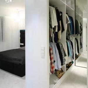 Obok sypialni znajduje się przestronna garderoba. Lustro na całej wysokości ściany optycznie powiększa przestrzeń. Proj. Dominik Respondek. Fot. Bartosz Jarosz.