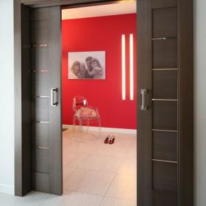 W przejściu pomiędzy pomieszczeniami zdecydowano się na montaż dwuskrzydłowych drzwi przesuwnych z systemem chowanym w ścianie. Dzięki takiemu rozwiązaniu zaoszczędza się dużo miejsca i zyskuje czystość przestrzeni. Bezpośrednio za drzwiami można postawić poręczny mebel lub zawiesić obrazek. Fot. Bartosz Jarosz.
