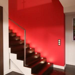 Klatkę schodową przysłania szklana ściana w stalowej konstrukcji. Dzięki takiemu rozwiązaniu możemy podziwiać piękne, drewniane schody na tle czerwonej ściany. W stopnicach zamontowano reflektorki świetlne ułatwiające poruszanie się po zmroku. Fot. Bartosz Jarosz.