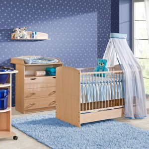 Meble o frontach imitujących jasne drewno w niebieskim wnętrzu tworzą uspokajającą aranżację. Z całością komponuje się błękitny dywan.  Fot. ATB Meble.