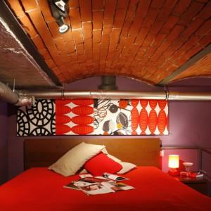 Efektowna rura od okapu kuchennego, wijąca się nad zagłówkiem łóżka - to niewątpliwie charakterystyczny element dekoracyjny mieszkania.  Fot. Marcin Onufryjuk.