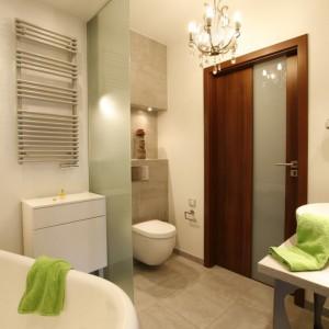 Szlachetną i surową estetykę łazienki przełamuje odbijający się w lustrze kryształkowy żyrandol. Fot. Marcin Onufryjuk.