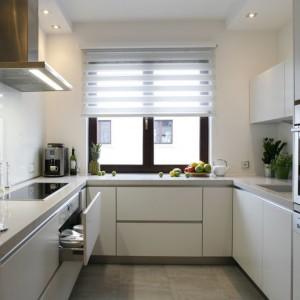Symetryczna zabudowa kuchni, uzupełniona szklanymi płaszczyznami, nietypowymi jeśli chodzi o barwę - to tzw. białe szkło lacobel. Fot. Marcin Onufryjuk.