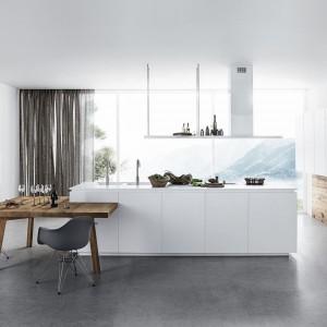 Kuchnia Cloe w nowoczesnym, minimalistycznym stylu. Na środku znajduje się funkcjonalna wyspa, po bokach zaś liczne szafki wykończone białym lakierem. Blat wykonany z Corianu, również w kolorze białym uzupełnia całość zabudowy. Ściana, na której wiszą półki wykończona jest fornirem. Wycena indywidualna, Cesar.