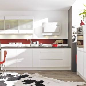 Zabudowa kuchenna z programu PN 300. Monochromatyczność białych mebli przełamuje czerwony kolor zastosowany na ścianie. Stanowi też ciekawy akcent dekoracyjny w zestawie z krzesłem w tej samej tonacji. Wycena indywidualna, Pino.