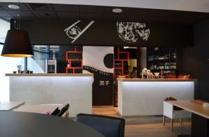 Właściciel lokalu wpadł na odważny pomysł połączenia dwóch tak odmiennych kuchni - japońskiej i włoskiej. Z takiej koncepcji powstała restauracja Gemelli Pizza Cafe i Futago Sushi. Nazwy w przetłumaczeniu oznaczają odpowiednio bliźnięta i bliźniak. Aranżacja łączy japońską prostotę i włoską elegancję. Obie aranżację przeplatają się i nie tworzą wyraźnej granicy tych dwóch światów. Inspiracją był symbol jin jang, który pojawia się w identyfikacji wizualnej lokalu. Świetlne japońskie kratownice, drewniane ścianki i sufit, proste tapicerowane siedziska i ażurowe lampy nad stolikami , to część sushi. Natomiast na części pizzy pojawiają się żyrandole i eleganckie krzesła w kolorze białym. Delikatnie wprowadzone zostały akcenty kolorystyczne.Zielona fototapeta z bambusami skrywa drzwi przesuwane za którymi znajdują się toalety. Smacznego!