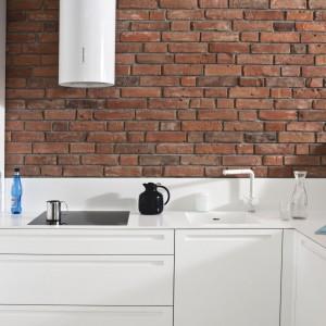 Zabudowa kuchenna model 022, w której białe, półmatowe, lakierowe fronty mebli oraz okap zostały ładnie wyeksponowane na tle ceglanej ściany. Fronty posiadają specjalnie odfrezowane uchwyty. Blat, również biały, wykonany jest z Corianu (grubość 13 cm). Wycena indywidualna, Zajc Kuchnie.