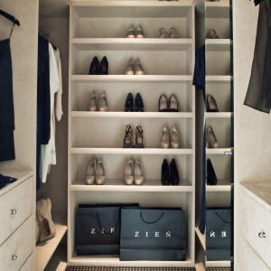 Przestronna garderoba projektu Zienia - wnętrza szuflad, szaf i szafek obite są beżową alcantarą. Fot. Ghelamco Poland.