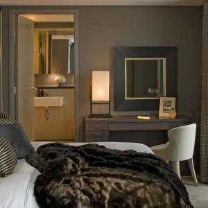 W trzech sypialniach na pierwszym poziomie poszczególne elementy, takie jak obita skórą ławka, obramowane hebanem i wykończone złotem lustro i printy stanowią nie tylko interesujące dodatki, ale też nadają pomieszczeniom indywidualny charakter. Fot. Richard Waite.