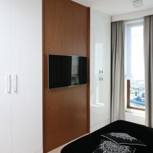 Zabudowa umieszczona na przeciwko łóżka została podzielona na dwie części poprzez panel z telewizorem. Proj. Anna Maria Sokołowska. Fot. Bartosz Jarosz.