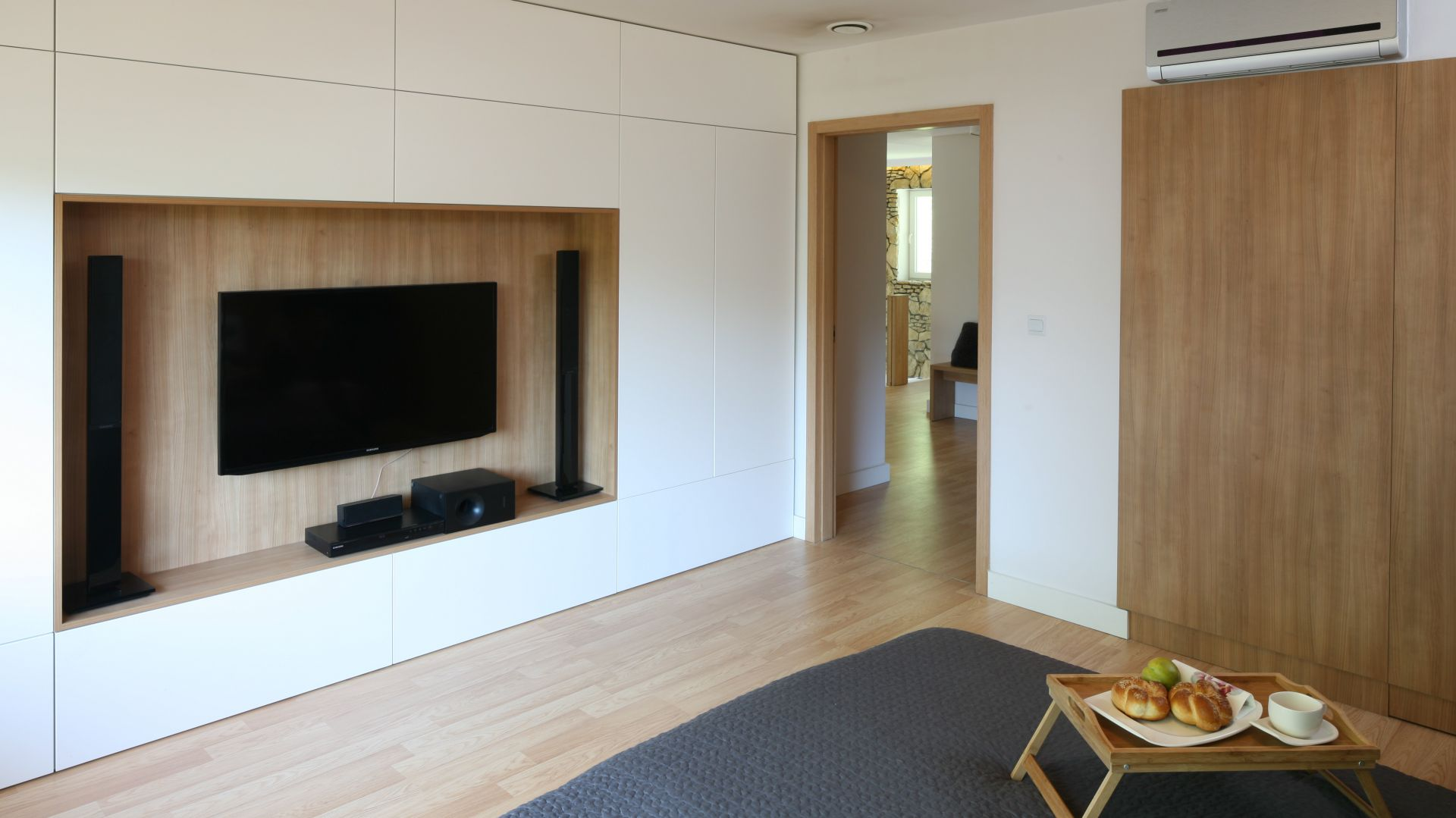 Miejsce na telewizor zostało zaprojektowane jako wnęka w białej zabudowie. Proj.Małgorzata Błaszczak. Fot. Bartosz Jarosz.