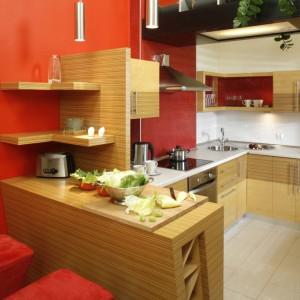 Czerwień w smakowitym odcieniu paprykowy w świetnym duecie z drewnianymi meblami kuchennymi. Proj. wnętrza Inside Lab.