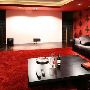 Pokój telewizyjny, wyposażony w projektor i duży rzutnik. Jego buduarowy, a może kinowy charakter to zasługa pięknych czerwieni, zestawionych w wieczorowym duecie z czernią. Proj. wnętrza Małgorzata Szajbel-Żukowska, Maria Żychiewicz.