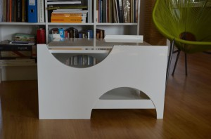 Stolik wykonany jest z płyty mdf lakierowanej w kolorze białym. Posiada szuflady, które służą również jako dodatkowe blaty stolika. W zależności od potrzeb zmienia się. Projekt stolika powstał na konkurs organizowany przez firmę Vox i zrealizowany w tym roku. Stolik można zakupić w dowolnej kolorystyce i w dowolnym materiale. W tej chwili powstaje wersja ze sklejki.