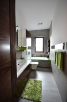 APARTAMENT 100 M/KW. W PODWARSZAWSKIM Józefosławiu. Zaprojektowany został w prostym, minimalistycznym stylu. Bazę większości pomieszczeń stanowi biel ścian i mebli,bielona podłoga ,skontrastowane z czernią i szarościami.Duża łazienka - łazienka rodzinna,z dużą wanną,baza materiałowa to szare płytki gresowe ocieplone zielenią mozaiki i fornirem z palisandru,pojawiającym się na frontach meblowych i drzwiach.