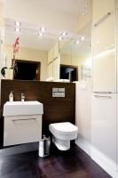 Mała łazienka optycznie powiększona lustrami, w szafkach z frontem lakierowanym w kolorze zbliżonym do płytek udało się ukryć pralkę.