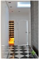 Ciemny hall został urządzony w na biało, przestrzeń powiększają białe lakierowane drzwi i szafy zlicowane ze ścianami.
