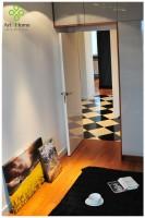W sypialni poza tapicerowanym łóżkiem znajduje się lakierowana na szaro duża szafa z drewnianymi elementami ocieplającymi wnętrze.