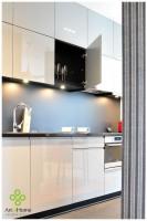 Kuchnia urządzona minimalistycznie z frontami z szarego lakierowanego MDF i czarnymi dodatkami. Również wnętrza szafek są czarne.