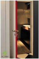 Łazienka urządzona konsekwentnie w szarościach i czerni, ocieplona drewnianym blatem pod umywalkami i czerwonym akcentem na krawędzi drzwi.