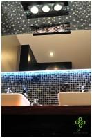 W łazience najważniejszym elementem jest błyszcząca ciemna metalowa mozaika podświetlona dekoracyjnym oświetleniem zza lustra.