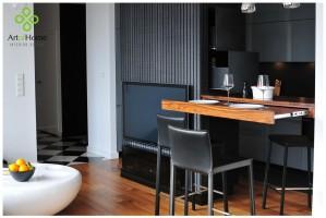 Minimalistyczny salon otwarty na kuchnię. Wielofunkcyjna ścianka dzieląca pomieszczenia jest podpora dla baru, który można przekształcić w stół jadalny.