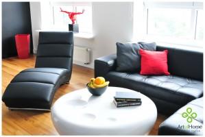 Kąt wypoczynkowy w salonie składa się z narożnika i wygodnego szezlonga z ekoskóry. Elementy te równoważone są przez podłogę w ciepłym miodowym odcieniu.