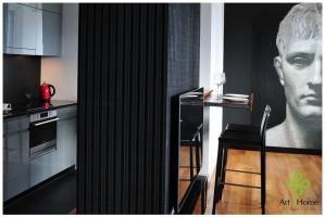 Ścianka dzieląca kuchnie z salonem pełni wiele funkcji - od strony kuchni miesza się tam schowki, od strony salonu szafka RTV, natomiast od strony blatu barowego, znajdują się szuflady/barek .