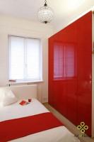 W sypialni dominantą jest pojemna czerwona lakierowana szafa. Elementem dekoracyjnym jest kryształowy żyrandol odnaleziony na targu staroci.
