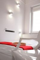 W sypialni przy niskim tapicerowanym białym łóżku zastosowano 3 dekoracyjne kinkiety asymetrycznie rozrzucone po ścianie.