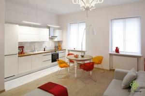 Salon połączony z aneksem kuchennym. Minimalistyczne białe lakierowane szafki komponują się z białymi ścianami. Zastosowanie szlachetnych materiałów jak marmur i gruba dębowa deska konweniuje z historycznym charakterem budynku.