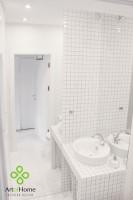 Mała łazienka została urządzona cała w bieli. Biała mozaika jest fugowana szarą fugą, aby zachować historyczny charakter wnętrza. Pomieszczenie powiększono zastosowaniem dwóch dużych luster.