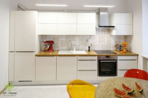 Kuchnia z minimalistycznymi białymi frontami, ożywiona została dębowym blatem oraz mozaiką nad nim z różnorodnych białych płytek. Obrazu dopełnia nowoczesne oszczędne oświetlenie.
