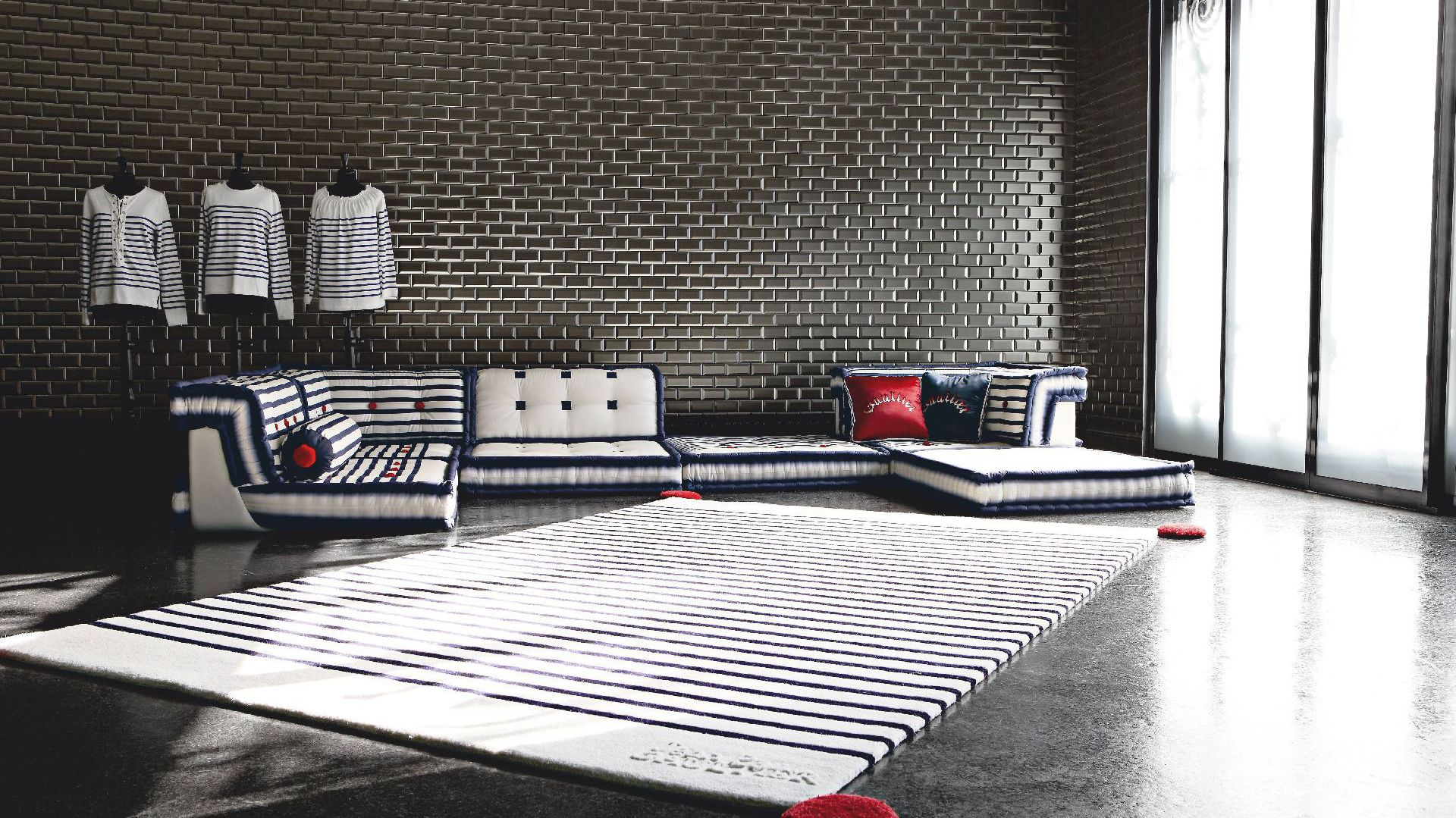 Modułowa sofa Mah Jong Matelot to kwintesencja stylu francuskiego projektanta. Uroku dodaje jej wykonane ręcznie obicie w zadziornej, rockowej stylistyce. Świetnie prezentuje się z dywanem w marynarskie paski. Fot. Roche Bobois.