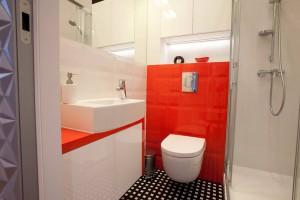 Łazienka w tonacji czerwono - białej.