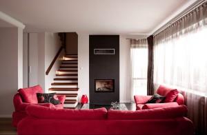 Jasny, przytulny salon z elegancką czerwienią.
