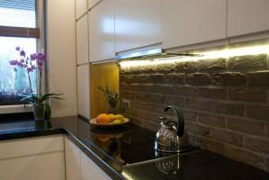 Czarno - biała kuchnia z cegłą na ścianie.
