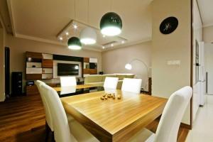 Prezentujemy przestrzeń otwartą (salon, kuchnia, jadalnia) wraz z łazienkami, w projektowanym przez nas mieszkaniu na Mokotowie. Wystrój wnętrza jest nowoczesny, stonowany kolor ścian i biel mebli została przełamana orzechowym drewnem i czarnymi elementami. Taka aranżacja umożliwia dość elastyczny dobór dodatków dekoracyjnych. Funkcjonalna zabudowa ściany z TV wraz z dużym wygodnym narożnikiem oraz dobrze zaplanowane oświetlenie tworzą przyjemny kącik wypoczynkowy.