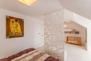 Sypialnia rodziców z wydzielonym tymczasowym miejscem dla najmłodszego członka rodziny.