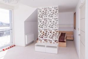 Sypialnia rodziców, łóżko za panelem dekoracyjnym.